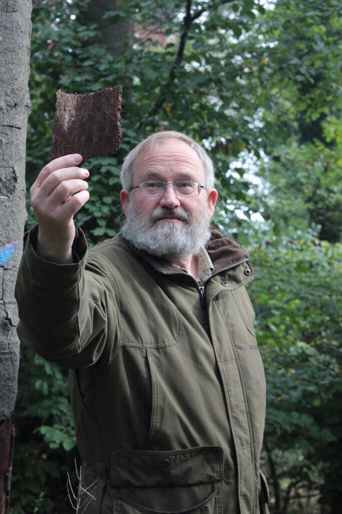 Förster Johannes Otto Lübke hält eine Buchenrinde in der Hand. Die dort sichtbaren Einbohrlöcher gleichen feinen Nadelstichen. Foto: M. Vogt
